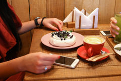 Girl sits and holds hands at table next to order of meringues, c Stock Photo