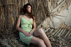 The girl sits at a house wall. In a green dress Royalty Free Stock Image
