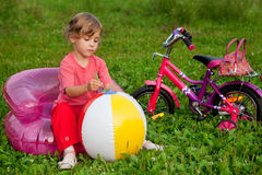 Girl sits in inflatable armchair in front of bike Stock Images