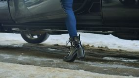 Girl sits inside car. Shooting from down. Close-up shooting. Girl wearing black shoes on high heels and jeans stands on winter dirty road near the black auto stock video footage