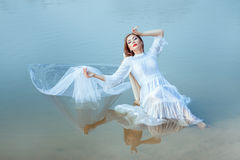 Girl sits on the lake and is reflected surface water. Royalty Free Stock Photos