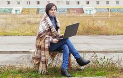 The girl sits with the laptop on a bench Stock Photography