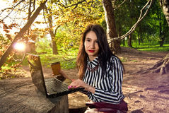 Girl sits with a laptop in the nature Stock Image