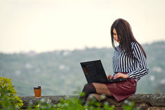 Girl sits with a laptop in the nature Royalty Free Stock Image