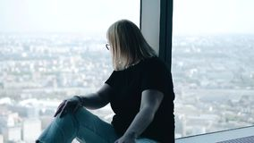 The girl sits at a large bright window and looks at the metropolis. stock video