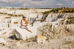 The girl sits on a large piece of marble , view of marble quarry Stock Images