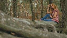 Girl sits in large pine tree forest roots slow motion stock video footage