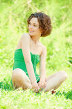 Girl sits on lawn Stock Photo