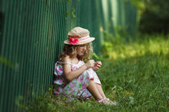 Girl sits leaning against a fence Stock Images