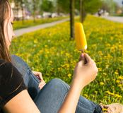 Girl with  ice cream. Girl sits leaning on a tree and eating ice cream surrounded with yellow dandelion flowers. Spring time Royalty Free Stock Photography