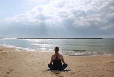 Girl meditating on the beach in the sun stock image