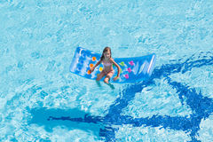 A girl sits on  mattress in the pool Stock Photo