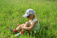 Girl sits on meadow Royalty Free Stock Photography