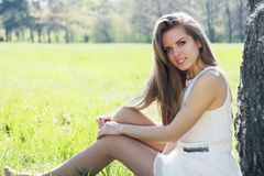 Girl sits in the meadow Stock Images