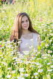 Girl sits on meadow with wild flowers Royalty Free Stock Image