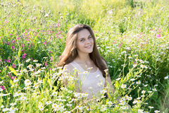 Girl sits on meadow with wild flowers Stock Photos