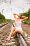 Girl sits on metal rails Stock Photography