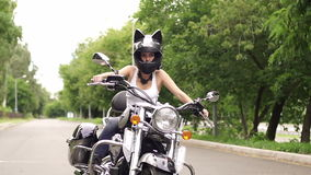 Girl sits on a motorcycle in helmet with cat ears. stock video