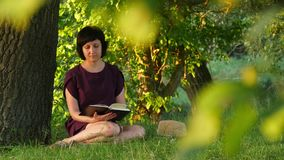 A girl sits near a tree and reads a book. 4k stock video