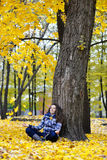 Girl sits near a tree, yellow leaves fall royalty free stock photography