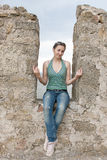 A girl sits in a niche of a stone wall. Photo Royalty Free Stock Images