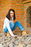 Girl sits at the old brick wall Royalty Free Stock Photo