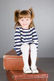 Girl sits on an old suitcase Royalty Free Stock Photography
