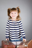 Girl sits on an old suitcase. Four-year beautiful girl has control over two old suitcases on a gray background Stock Photos