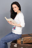A girl sits on an old suitcase and reading a book. The girl in jeans and a white sweater Royalty Free Stock Photography