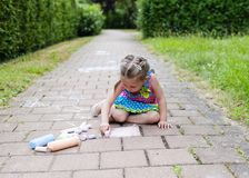 Free Girl Sits On Concrete Asphalt Square Road. Child Drawings Paintings On Asphalt Concrete. Side View Stock Photo - 120624380