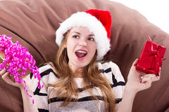 Girl sits onchair with a gift in her hands Stock Images