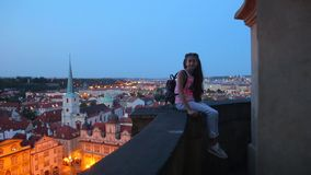 Girl sits parapet on the background of night city stock footage