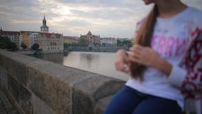 Girl sits on the parapet of the bridge and touches hair stock video footage