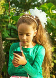 Girl sits in park and plays with cell phone Royalty Free Stock Photography