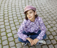 Girl sits on the pavement. Girl in a cap sits on the pavement Royalty Free Stock Photos