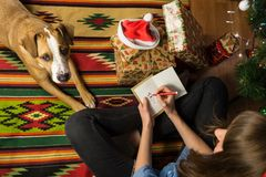 Young female person draws a funny holiday stick figure on a greeting card and writes congratulation on happy Christmas holiday. Girl sits with pet dog and signs royalty free stock photography