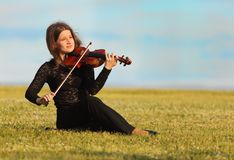 Girl sits and plays violin against  sky Stock Photos