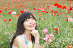 Girl sits in poppy field Royalty Free Stock Photo