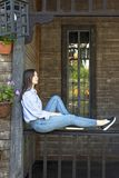 Girl sits on the porch of a wooden house stock photo