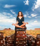 Girl sits in a pose of yoga on suitcases. Royalty Free Stock Photo