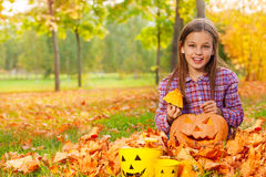 Girl sits with pumpkin in the autumn forest Stock Image