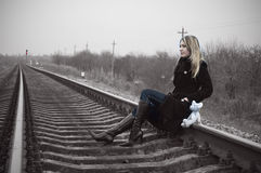 The girl sits on rails with a toy Royalty Free Stock Photos