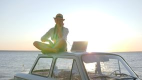 Girl sits on retro car roof in backlight talking on cellphone and holds solar array, young woman using powered solar stock video footage