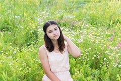 Girl sits on richly meadow Royalty Free Stock Photo