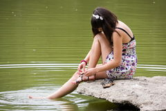A girl sits at the river Royalty Free Stock Photos