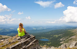 Girl sits on a rock Stock Photography