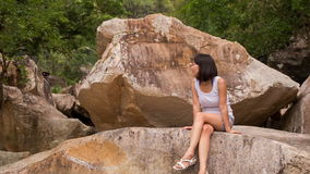 Girl sits on rock admires scenery of stones and mountain stream stock video footage