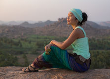 The girl sits on a rock and admires the stony scenery at sunset. The asian girl sits on a rock and admires the stony scenery at sunset Stock Photos