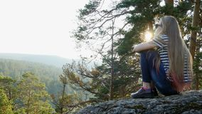 Girl sits on a rock stock footage