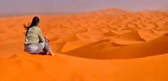 Girl sits on a sandy dune Stock Image